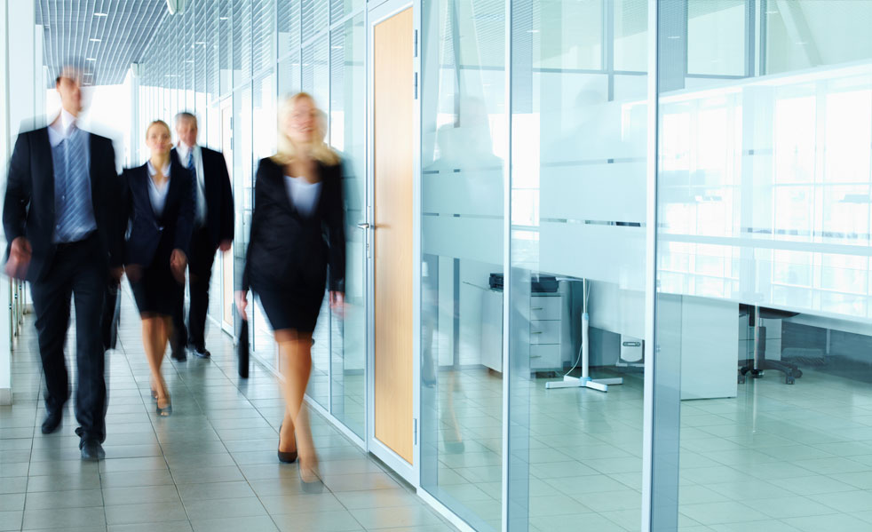 Employees walking down a hall with glass rooms